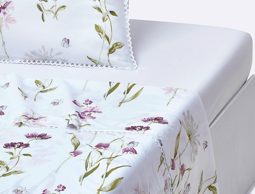 Un drap orné de dentelle imprimé de fleurs et de papillons aux tons délicats sur fond blanc. Percale 100% coton.