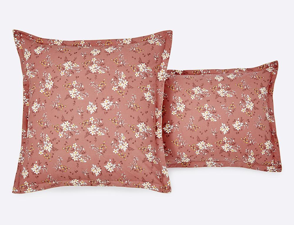 Une taie d'oreiller romantique associant imprimé fleuri et un uni rose cuivré. Finition passepoil et petit volant plat.