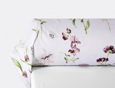 Une taie de traversin percale ornée de dentelle imprimée de fleurs et de papillons aux tons délicats sur fond blanc.
